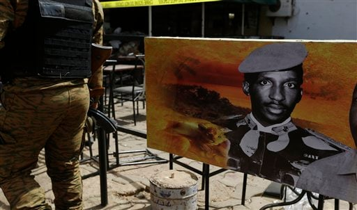 A soldier walks past a poster of former president of Burkina Faso, Thomas Sankara, outside a bar that was attacked in Ouagadougou, Burkina Faso, Sunday, Jan. 17, 2016. The overnight seizure of a luxury hotel in Burkina Faso's capital by al-Qaida-linked ex