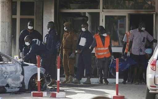 Rescue workers carry a body from the Splendid Hotel in Ouagadougou, Burkina Faso, Saturday, Jan. 16, 2016. The overnight seizure of a luxury hotel in Burkina Faso's capital by al-Qaida-linked extremists ended Saturday when Burkina Faso and French security