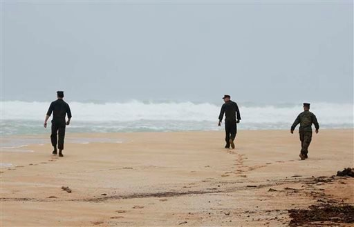 This Friday, Jan. 15, 2016, photo provided by the U.S. Marine Corps shows Marines attached to Marine Heavy Helicopter Squadron 463 search for debris of a helicopter mishap in Haliewa Beach Park, Hawaii. Rescuers battled winds of up to 23 mph and waves up