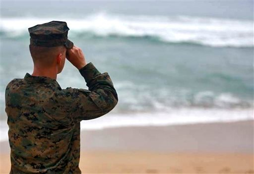 This Friday, Jan. 15, 2016 photo provided by the U.S. Marine Corps shows a Marine Officer attached to Marine Heavy Helicopter Squadron 463 uses binoculars to search for debris of a helicopter mishap in Haliewa Beach Park, Hawaii. Rescuers battled winds of
