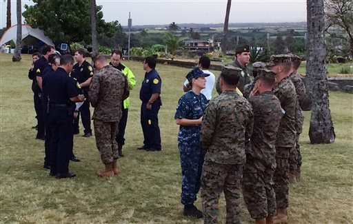 Military officials and Honolulu Police Department officers talk at a beach park where search and rescue officials are meeting in Haleiwa, Hawaii, Friday, Jan. 15, 2016, after two U.S. Marine helicopters carrying 12 crew members collided off the Hawaiian i