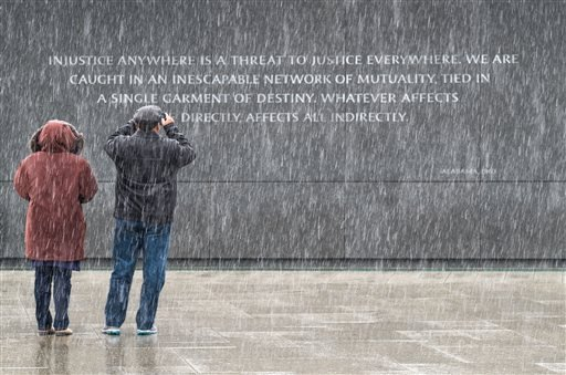 Visitors at the Martin Luther King, Jr. Memorial in Washington stop to photograph the quotes etched into the memorial's back wall while it snows in the Nation's Capital, Jan. 17, 2016. (AP Photo/J. David Ake)