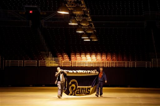 1/141/16 file photo: Jack Dungey, rt, and Jim McNeely, decorators with Local 39, carry away the 1999 Super Bowl championship banner after it was removed from the Edward Jones Dome, former home of the St. Louis Rams football team.(AP Photo/Jeff Roberson)
