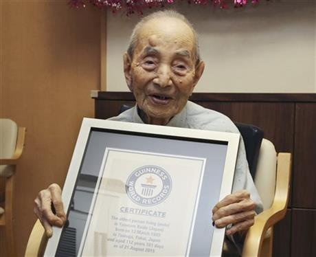Yasutaro Koide, 112, holds the Guinness World Records certificate as he is formally recognized as the world's oldest man at a nursing home in Nagoya, central Japan. Koide, who was born on March 13, 1903, has died on Tuesday, Jan. 19, 2016. AP