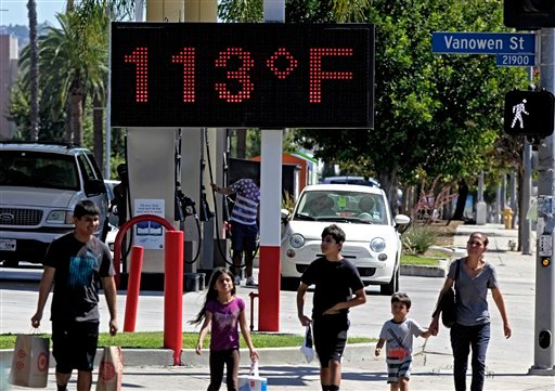 In this Aug. 15, 2015 file photo, pedestrians walk past a digital thermometer reading 113 degrees Fahrenheit in the Canoga Park section of Los Angeles. Earth last year wasn't just the hottest year on record, but it left a century of temperature high mark
