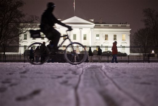 A bicyclist rides past the White House during evening snowfall in Washington,Wednesday, Jan. 20, 2016. As Washington prepares for this weekend's snowstorm, now forecast to reach blizzard conditions, a small clipper system pushed through the region Wednesd