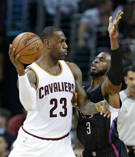 Cleveland Cavaliers' LeBron James (23) passes over Los Angeles Clippers' Chris Paul (3) in the second half of an NBA basketball game Thursday, Jan. 21, 2016, in Cleveland.