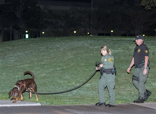 Orange County sheriff's deputies and a search dog investigate early Saturday morning, Jan. 23, 2016, after three jail inmates charged with violent crimes escaped from Central Men's Jail in Santa Ana, Calif.