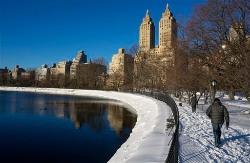 Visitors to New York's Central Park pass the Jacqueline Kennedy Onassis Reservoir Sunday, Jan. 24, 2016, in the wake of a storm that dumped heavy snow along the East Coast. (AP Photo/Craig Ruttle)