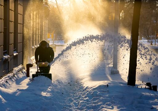 Snow is cleared along a street in the Upper West Side neighborhood of New York Sunday, Jan. 24, 2016, in the wake of a storm that dumped heavy snow along the East Coast. (AP Photo/Craig Ruttle)