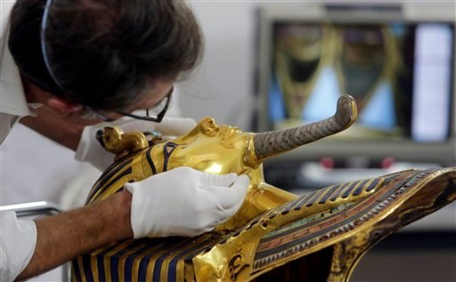 In this Tuesday, Oct. 20, 2015 file photo, German restorer Christian Eckmann begins restoration work on the golden mask of King Tutankhamun over a year after the beard was accidentally broken off and hastily glued back with epoxy, at the Egyptian Museum i