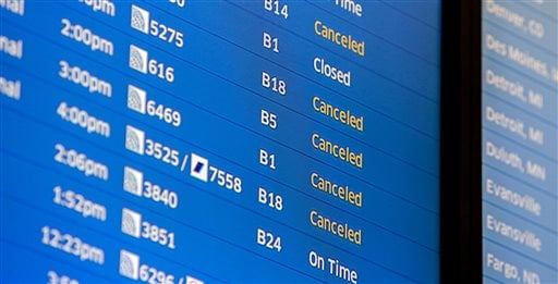 Flight boards at O'Hare International Airport show cancellations Friday, Jan. 22, 2016 in Chicago. Airlines at Chicago's two major airports have canceled 215 flights largely due to a blizzard threatening down on the East Coast. (AP Photo/Teresa Crawford)