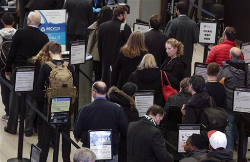 Travelers wait in a security line at O'Hare International Airport Friday, Jan. 22, 2016 in Chicago. Airlines at Chicago's two major airports have canceled 215 flights largely due to a blizzard threatening down on the East Coast. (AP Photo/Teresa Crawford)