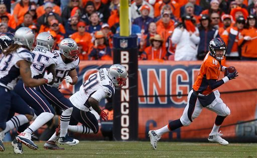 Denver Broncos quarterback Peyton Manning is chased out of the pocket by New England Patriots defenders during the first half the NFL football AFC Championship game between the Denver Broncos and the New England Patriots, Sunday, Jan. 24, 2016, in Denver.