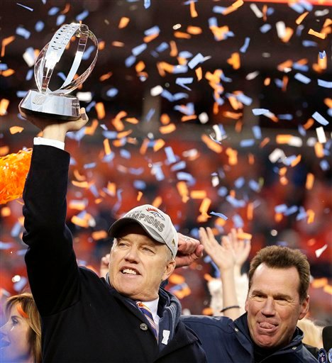 Denver Broncos general manager and executive vice president of football operations John Elway, left, is flanked by head coach Gary Kubiak as he holds the AFC Championship trophy following the NFL football AFC Championship game between the Denver Broncos a