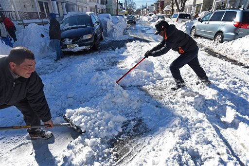 Angelo Delacrus, 15, right, of Passaic, who came from Dominican Republic recently, shovels snow in the middle of Van Buren Street in Passaic, N.J., Sunday, Jan. 24, 2016. (Kevin R. Wexler/The Record of Bergen County via AP)