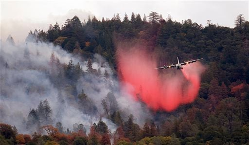 In this Sept. 15, 2015, file photo, a firefighting plane drops a load of fire retardant over a smoldering hillside in Middletown, Calif.