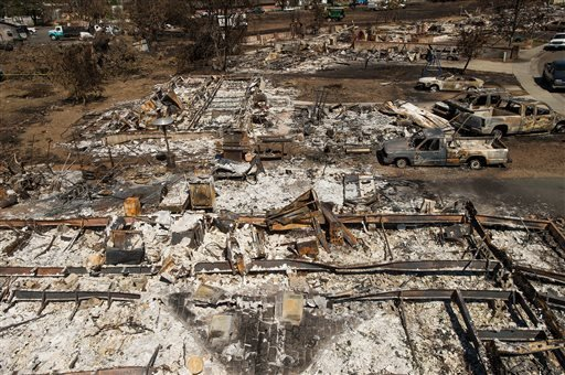 This Sept. 21, 2015, file photo shows remains of homes and vehicles scorched by a wildfire in Middletown, Calif.