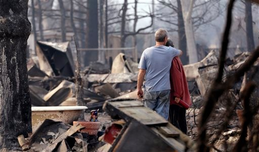 In this Sept. 15, 2015 file photo, Richard and Kathie Reeves embrace as they stand in the remains of the home of close friends that was destroyed in a wildfire several days earlier in Middletown, Calif.