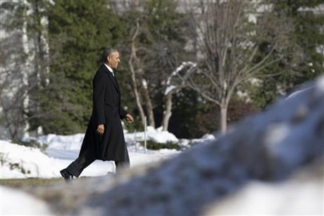 President Obama walks past piled snow toward the South Lawn of the White House in Washington, Monday, Jan. 25, 2016, to board Marine One en route to Walter Reed National Military Medical Center in Bethesda, Md., to visit with wounded service members. AP