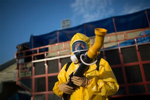 A health worker stands in the Sambadrome as he sprays insecticide to combat the Aedes aegypti mosquitoes that transmit the Zika virus, in Rio de Janeiro, Brazil, Tuesday, Jan. 26, 2016. Inspectors began to spray insecticide around the Sambadrome, the outd