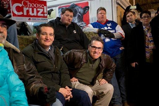 Former Texas Gov. Rick Perry, center, bites his lips as he gets up to introduce Republican presidential candidate, Sen. Ted Cruz, R-Texas, left, at a campaign event at High Point Bulls Oswald Barn, Tuesday, Jan. 26, 2016, in Osceola, Iowa. (AP Photo/Jae C