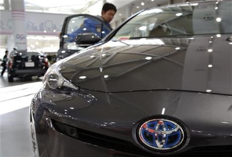 A visitor checks out Toyota Prius at a Toyota showroom in Tokyo, Wednesday, Jan. 27, 2016. Toyota Motor Corp. says it sold 10.151 million vehicles in 2015, retaining its status as the world's top-selling automaker for the fourth straight year. (AP Photo)