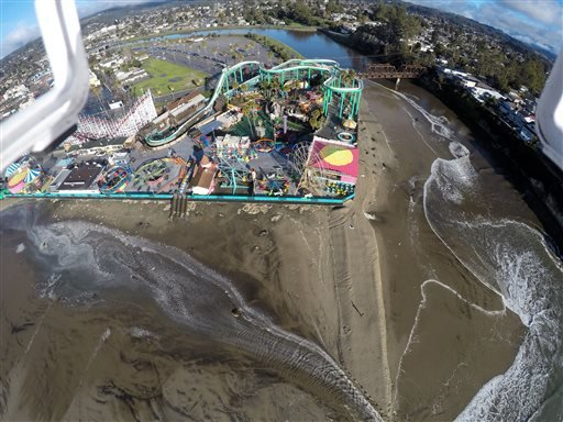 This Jan. 7, 2016 photo provided by The Nature Conservancy shows the San Lorenzo River overflowing around the Santa Cruz Beach Boardwalk, an oceanfront amusement park in Santa Cruz, Caif. The Nature Conservancy an environmental group in California is recr