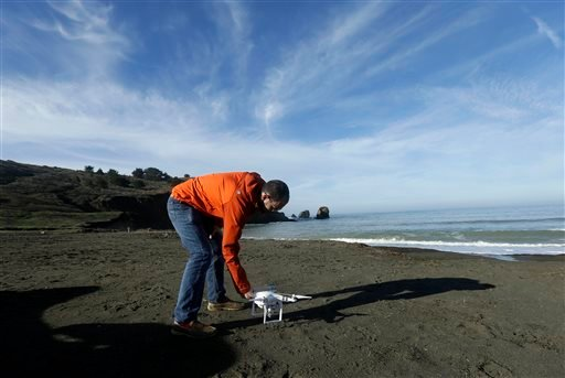 In this Thursday, Jan. 21, 2016 photo, Trent Lukaczyk, an unmanned aerial vehicle (UAV) engineer who builds and flies drones to monitor changes in the ocean environment, sets up a DJI Phantom 3 Advanced drone to take photos and videos over the coastline i