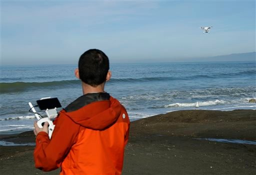 In this Thursday, Jan. 21, 2016 photo, Trent Lukaczyk, an unmanned aerial vehicle (UAV) engineer who builds and flies drones to monitor changes in the ocean environment, controls a DJI Phantom 3 Advanced drone to take photos and videos over the coastline