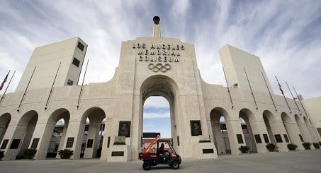 A worker rides past the entrance of The Los Angeles Memorial Coliseum on Wednesday, Jan. 13, 2016.