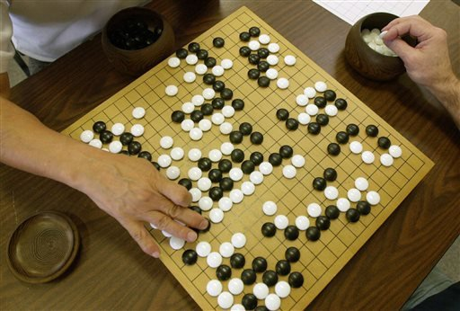 A player places a black stone while his opponent waits to place a white one as they play Go, a game of strategy, in the Seattle Go Center, Tuesday, April 30, 2002. The game, which originated in China more than 2,500 years ago, involves two players who tak