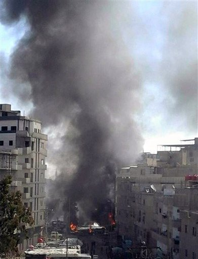 In this photo released by the Syrian official news agency SANA, smoke rises after three bombs exploded in Sayyda Zeinab, a predominantly Shiite Muslim suburb of the Syrian capital, Syria, Sunday, Jan. 31, 2016. The triple bombing claimed by the extremist