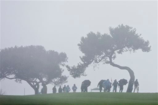 Golf fans leave the course during a weather delay in the final round of the Farmers Insurance Open golf tournament Sunday, Jan. 31, 2016, in San Diego. (AP Photo/Gregory Bull)