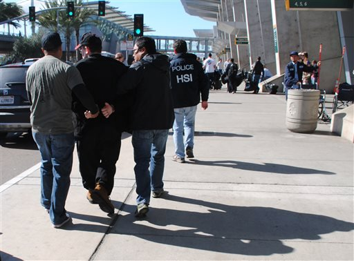In this Friday, Jan. 29, 2016 photo provided by the U.S. Immigration and Customs Enforcement (ICE), former Columbus, Ohio, seminarian Joel Wright, second left, is arrested at San Diego's airport in San Diego on federal charges for allegedly seeking to hav