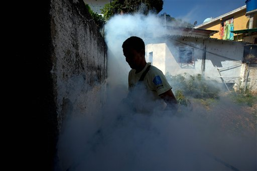A Sucre municipality worker fumigates for Aedes aegypti mosquitoes that transmit the Zika virus in the Petare neighborhood of Caracas, Venezuela, Monday, Feb. 1, 2016. Venezuela is reporting a jump in cases of a rare, sometimes paralyzing syndrome that ma