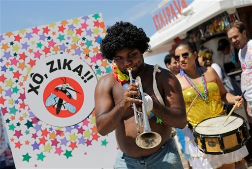 "Musicians play samba at a street carnival parade during which health workers distributed kits with information about the Zika virus, on Ipanema beach in Rio de Janeiro, Brazil, Sunday, Jan. 31, 2016. The sign reads in Portuguese : ""Get out Zika."" Original"