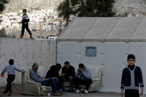 Refugees check their cell phones as a child runs atop of a cement wall at a small refugee camp at Pothia port, on the southeastern Greek island of Kalymnos, Monday, Feb. 1, 2016. European countries have been strained by the influx of migrants, leading to