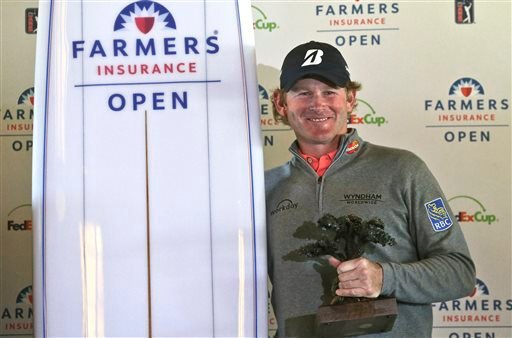 Brandt Snedeker holds the Framers Insurance Open trophy and a ceremonial surfboard after the final round of the Farmers Insurance Open golf tournament Monday, Feb. 1, 2016, in San Diego. Snedeker finished his final round Sunday before it was suspended bec