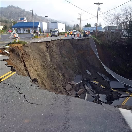 This Jan. 28, 2016, photo provided by the Oregon Department of Transportation shows a massive sinkhole that has opened up on a road near Highway 101 in the Curry County town of Harbor, Ore. Signs have been placed along the highway directing traffic to a d