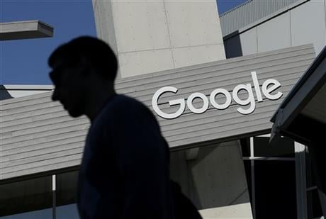 In this Nov. 12, 2015, file photo, a man walks past a building on the Google campus in Mountain View, Calif. Alphabet Inc., Google's holding company, reports financial results Monday, Feb. 1, 2016. (AP Photo/Jeff Chiu, File)