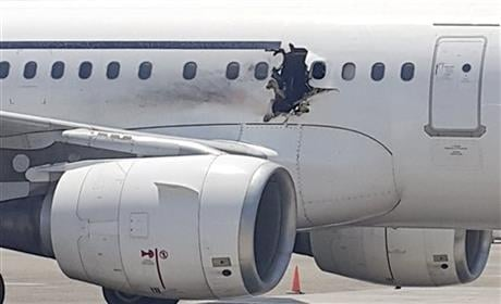 A gaping hole in the commercial airliner forced it to make an emergency landing at Mogadishu's international airport late Tuesday, officials and witnesses said. (AP Photo)