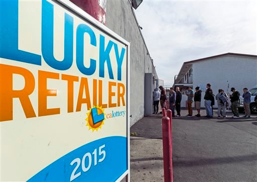 In this Jan. 13, 2016 file photo, a California Lucky Retailer sign is posted outside the Blue Bird Liquor store as customers wait in line to buy lottery tickets in Hawthorne, Calif.