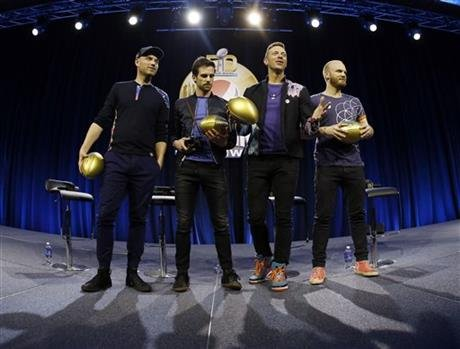 Jonny Buckland, left to right, Guy Berryman, Chris Martin and Will Champion of Coldplay hold footballs during a halftime news conference for the upcoming NFL Super Bowl 50 football game Thursday, Feb. 4, 2016, in San Francisco. (AP Photo/Matt Slocum)