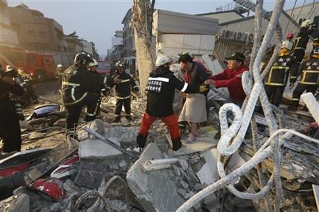 The 6.4-magnitude earthquake struck southern Taiwan early Saturday, toppling at least one high-rise residential building and trapping people inside. Firefighters rushed to pull out survivors. (AP Photo)