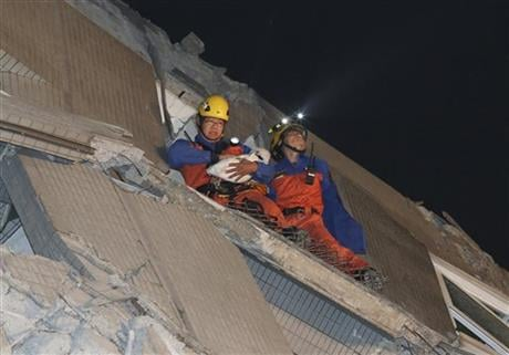 Rescue workers carry a baby swaddled in a cloth from the rubble of a toppled building after an earthquake in Tainan, Taiwan. AP