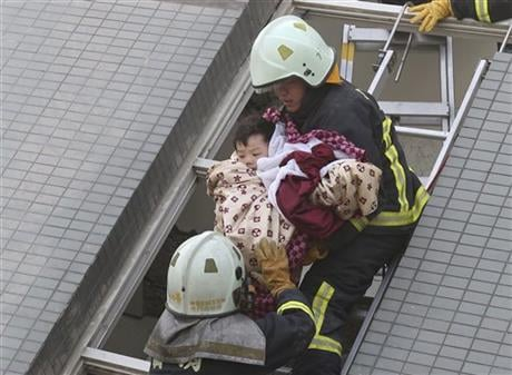 A child is rescued from a toppled building after a 6.4-magnitude earthquake in Tainan, Taiwan, Saturday, Feb. 6, 2016. The earthquake struck southern Taiwan early Saturday, toppling at least one high-rise residential building and trapping people inside.AP