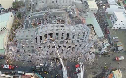 In this photo taken from a drone mounted camera, rescue workers search a collapsed building from an early morning earthquake in Tainan, Taiwan, Saturday, Feb. 6, 2016.