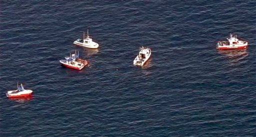 In this still frame from video provided by KABC-TV, a flotilla of boats search for wreckage from two small planes that collided in midair and plunged into the ocean off of Los Angeles harbor Friday, Feb. 5, 2016.