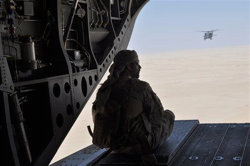In this Monday, Sept. 14, 2015 file photo, an Emirati soldier stands guard out the rear gate of a Chinook military helicopter, escorted by a Blackhawk helicopter, traveling from Saudi Arabia to Yemen. Saudi Arabia's offer to put boots on the ground to fig